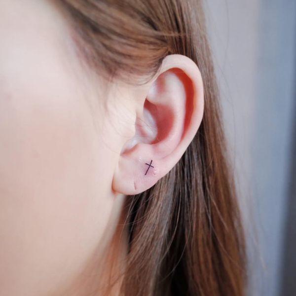 Cute Small Cross On Ear Tattoo Idea