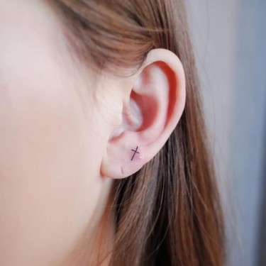 Cute Small Cross On Ear Tattoo