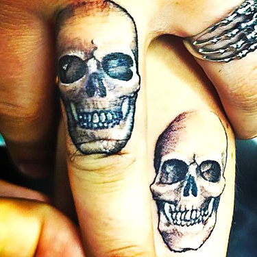 Matching Skulls on Middle Finger Tattoo