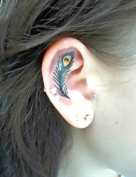 Tiny Peacock Feather on Ear Tattoo Idea