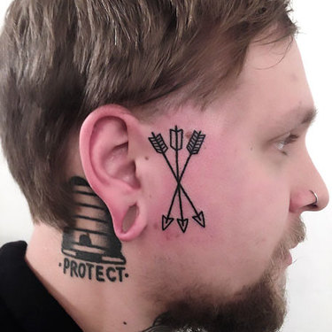 Small Arrows on Face Tattoo